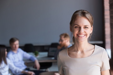 Portrait of smiling millennial worker posing for company photoshoot at business meeting in office, happy beautiful female employee look in camera making picture during teambuilding in boardroom