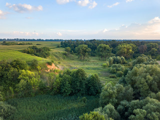 Wall Mural - Aerial view from the drone of a natural landscape with greenery, forest, field, ravine on a background of a cloudy sky.