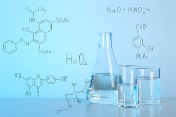 Laboratory glassware with liquids for analysis on table and chemical formulas against blue background