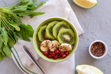 Breakfast spinach smoothie bowl with kiwi, banana, cranberries and flax seeds.
