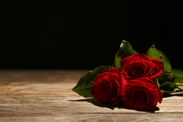 Beautiful red roses on table against black background. Funeral symbol