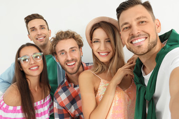 Group of happy young people taking selfie on white background