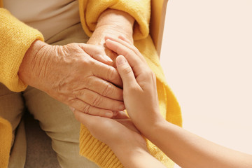 Helping hands on light background, closeup. Elderly care concept