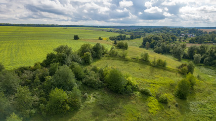 Wall Mural - Summer rural landscape with green fields, meadows, forests against cloudy background. Aerial view from drone.