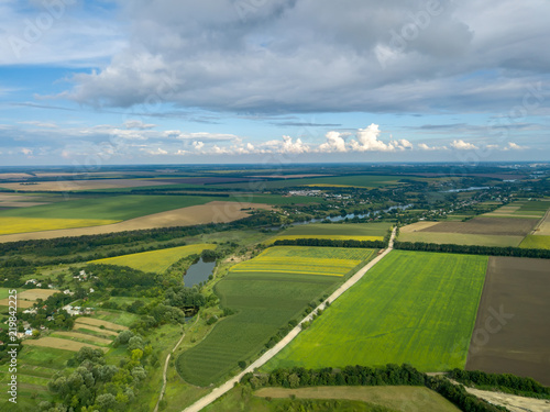 Wall mural Panoramic view from drone to the countryside with a country buildings, dirt road and agricultural fields against cloudy sky in the summer at sunset.