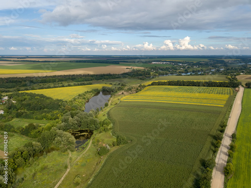 Wall mural Panoramic view from drone to the countryside with a river, dirt road and agricultural fields against cloudy sky