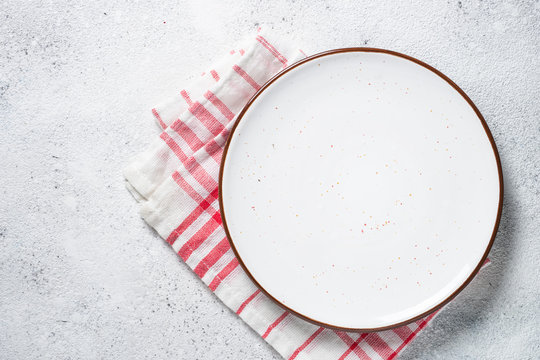 White plate and napkin on stone table top view.