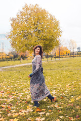 Smiling woman having fun in autumn park outdoors. Real people portrait