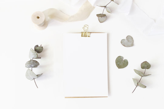 Feminine wedding desktop stationery mockup with blank greeting card, dry eucalyptus leaves, silk ribbon and golden binder clip on white table background. Flat lay, top view. Styled stock photo.