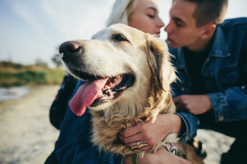 Beautiful romantic couple is having fun with their dog labrador retriever outdoors