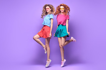 Wall Mural - Two Girl Jumping Fooling Around. Young Beautiful Model Woman Having Fun Dance in Fashion Stylish Outfit, Happy positive emotion. Cheerful Cool Sisters Friends on Purple