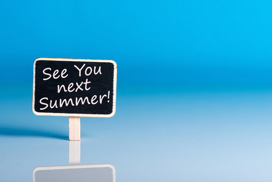 See you next Summer written on a note at the office table with empty space for text