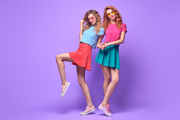 Wall Mural - Full-length portrait Two Girl with Wavy Hairstyle Having Fun Dance. Young Beautiful Hipster Model Woman in Fashion Stylish Summer Outfit. Crazy Sisters Friends on Purple