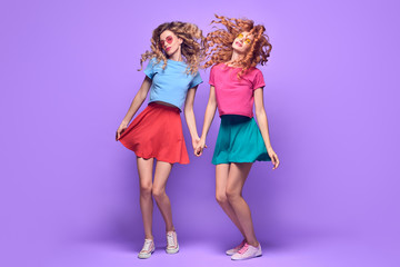 Wall Mural - Two Girl Jumping Fooling Around. Young Beautiful Model Woman Having Fun Dance in Fashion Stylish Outfit, Crazy positive mood. Cheerful Cool Sisters Friends on Purple