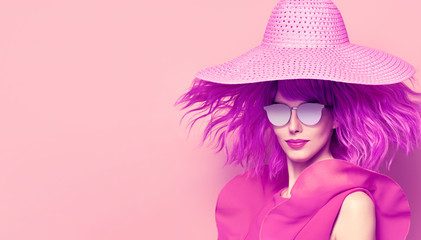 Young Beautiful Woman in Pink Summer Dress, Party Purple Hairstyle. Fashion Studio Portrait Glamour Lady. Playful Model Girl in Stylish Hat, Trendy Sunglasses. Creative Art