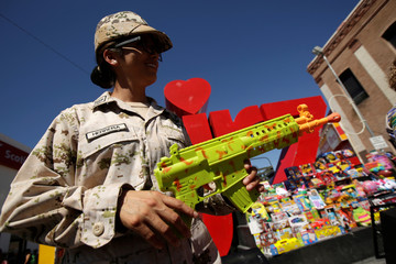 A female soldier holds a toy rifle during an exchange of toy weapons for toys as part of the campaign 'Playing without violence' organised by the Mexican Army in Ciudad Juarez