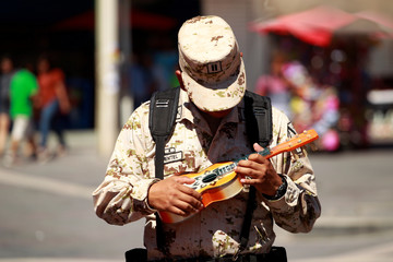 A soldier holds a guitar during an exchange of toy weapons for toys as part of the campaign 'Playing without violence' organised by the Mexican Army in Ciudad Juarez