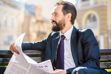 Handsome smiling businessman reading a newspaper outdoors