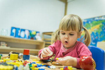 Little caucasian girl playing with wooden puzzle