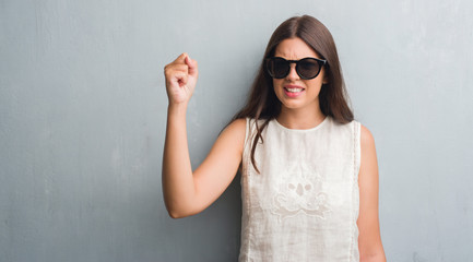 Young brunette woman over grunge grey wall wearing fashion sunglasses annoyed and frustrated shouting with anger, crazy and yelling with raised hand, anger concept