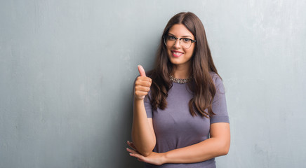 Young brunette woman over grunge grey wall wearing glasses happy with big smile doing ok sign, thumb up with fingers, excellent sign