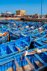 A fleet of blue fishing boats huddled together in the port of Essaouira in Morocco. You can also see the fortifications and a tower of the citadel of Mogador