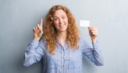 Young redhead woman over grey grunge wall holding blank visit card surprised with an idea or question pointing finger with happy face, number one