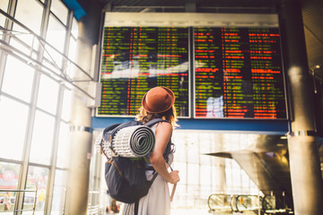 Theme travel public transport. young woman standing with back in dress and hat behind backpack and camping equipment for sleeping, insulating mat looks schedule on scoreboard airport station Fototapete