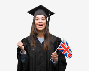 Young hispanic woman wearing graduated uniform holding flag of united kingdom screaming proud and celebrating victory and success very excited, cheering emotion