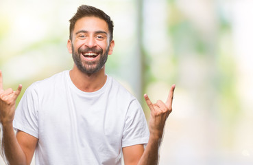 Adult hispanic man over isolated background shouting with crazy expression doing rock symbol with hands up. Music star. Heavy concept.