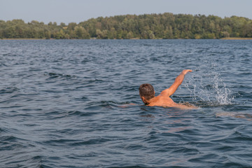 Young man swimming in the lake