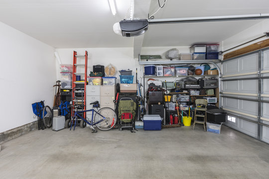 Cluttered but organized clean suburban residential two car garage with tools, file cabinets and sports equipment.