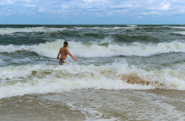 swim during a storm at sea, girl bathes in the sea waves