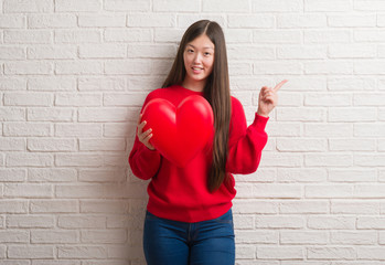 Young Chinese woman in love over brick wall holding red heart very happy pointing with hand and finger to the side