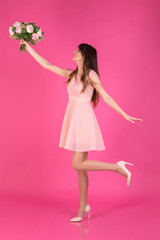 A young girl in a festive dress is catching a bouquet of flowers on a pink background