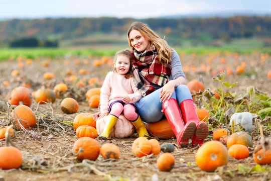 Little kid girl and beautiful mother having fun with farming on a pumpkin patch. Traditional family festival with children, thanksgiving and halloween concept. Cute farmers, woman with daughter.