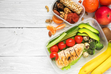 school lunch boxes with chicken, avocado, eggs and fresh vegetables, nuts and fruits on white wooden background