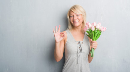 Caucasian adult woman over grey grunge wall holding pink flowers doing ok sign with fingers, excellent symbol