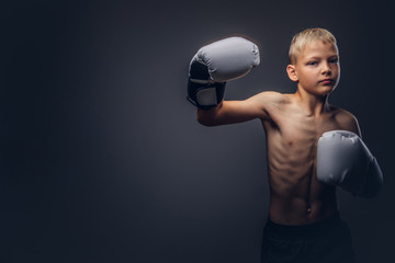 Shirtless young boxer with blonde hair wearing boxing gloves shows a boxing hook.
