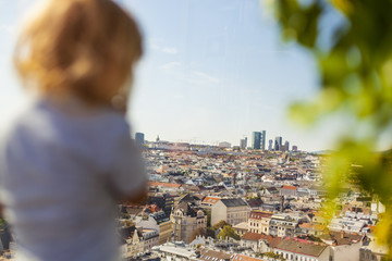 Kleines Kind schaut auf Stadtpanorama. Little child looking on city skyline. Girl looks at the city.
