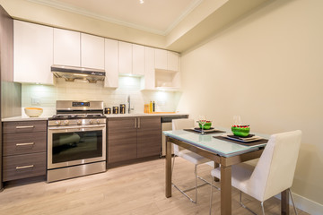 Modern, bright, clean kitchen interior with stainless steel appliances and dinner table in a luxury apartment.