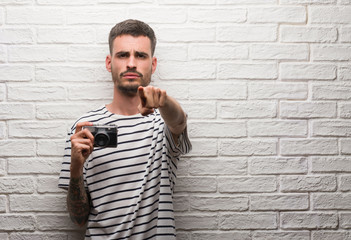 Young man holding vintage camera standing over white brick wall pointing with finger to the camera and to you, hand sign, positive and confident gesture from the front