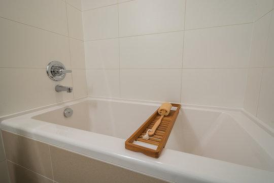 Fragment of luxury bathroom with wood bathroom caddy.