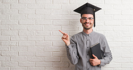 Young adult man over brick wall wearing graduation cap very happy pointing with hand and finger to the side