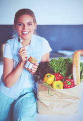 Keuken foto achterwand Keuken Young woman holding grocery shopping bag with vegetables .Standing in the kitchen