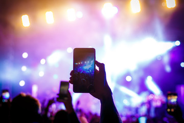 Hand with a smartphone on a live music festival, concert