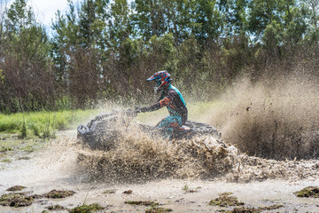 ATV Quad rides fast on big dirt and makes splashes of dirty water