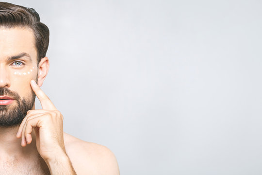 Skin care. Handsome young shirtless man applying cream at his face and looking at himself while standing over gray background and looking at camera. Close-Up. Space for text.