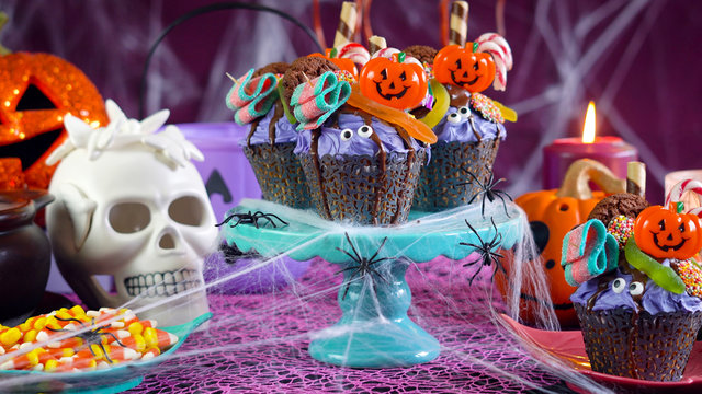 Happy Halloween candyland drip cake style cupcakes with lollipops and candy in party table setting.