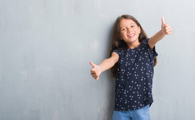 Young hispanic kid over grunge grey wall approving doing positive gesture with hand, thumbs up smiling and happy for success. Looking at the camera, winner gesture.